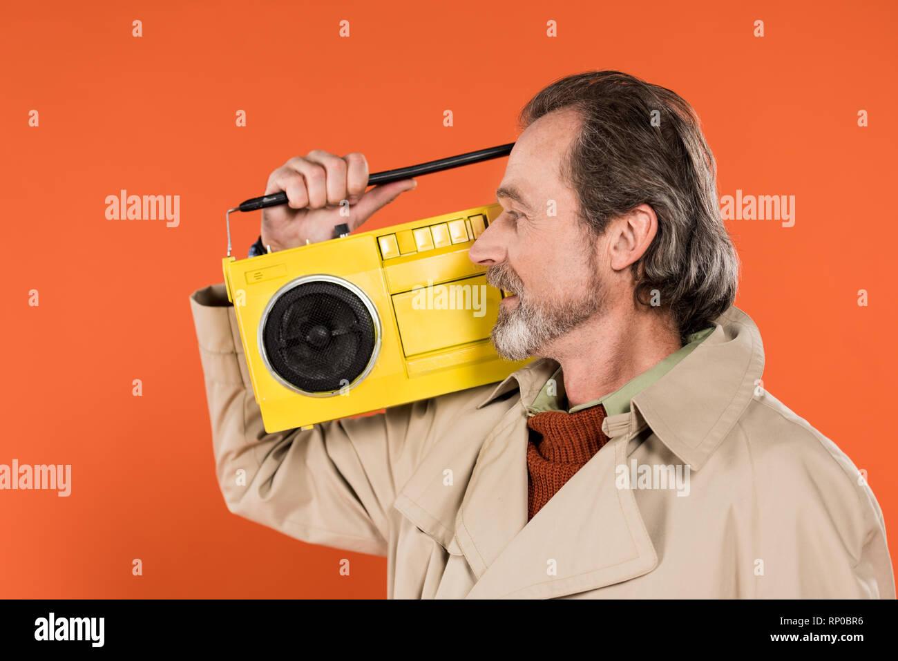 Allegro pensionato uomo guardando boombox giallo isolato su Orange Immagini  Stock 2d5fd9b379c5