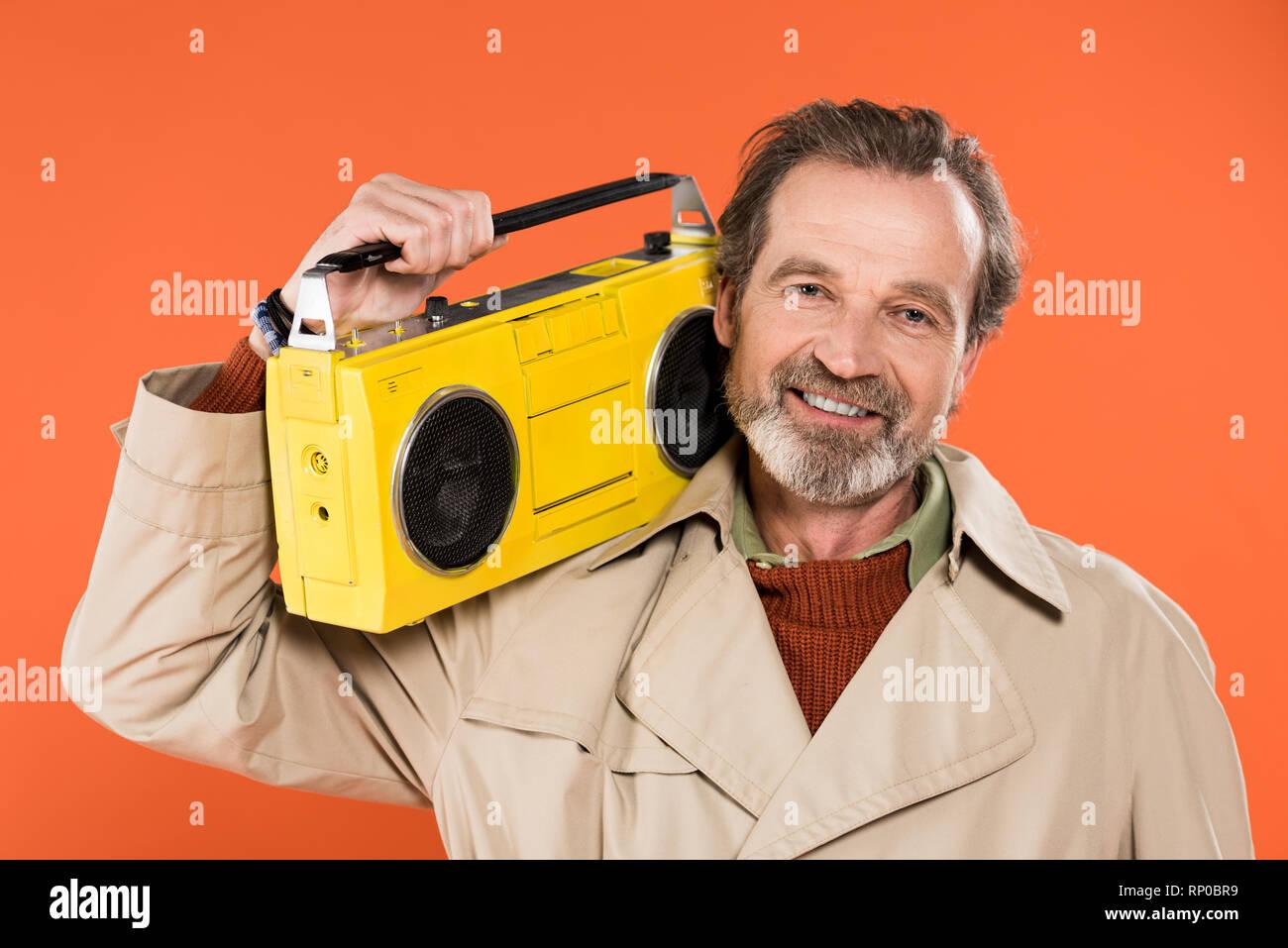 Allegro senior man holding boombox giallo isolato su Orange Immagini Stock 61cb1a1f62ff