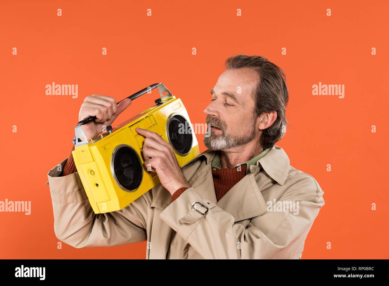 Allegro pensionato uomo toccando boombox giallo isolato su Orange Immagini  Stock 4797d6dfe594