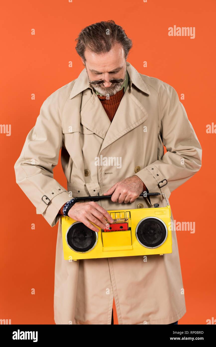 Allegro pensionato uomo premendo il pulsante giallo boombox isolati su  Orange Immagini Stock 434bf7972826