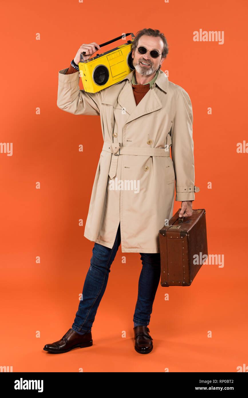 Allegro ritirò man holding boombox giallo e valigetta in mani su sfondo  arancione Immagini Stock fd7a62040152