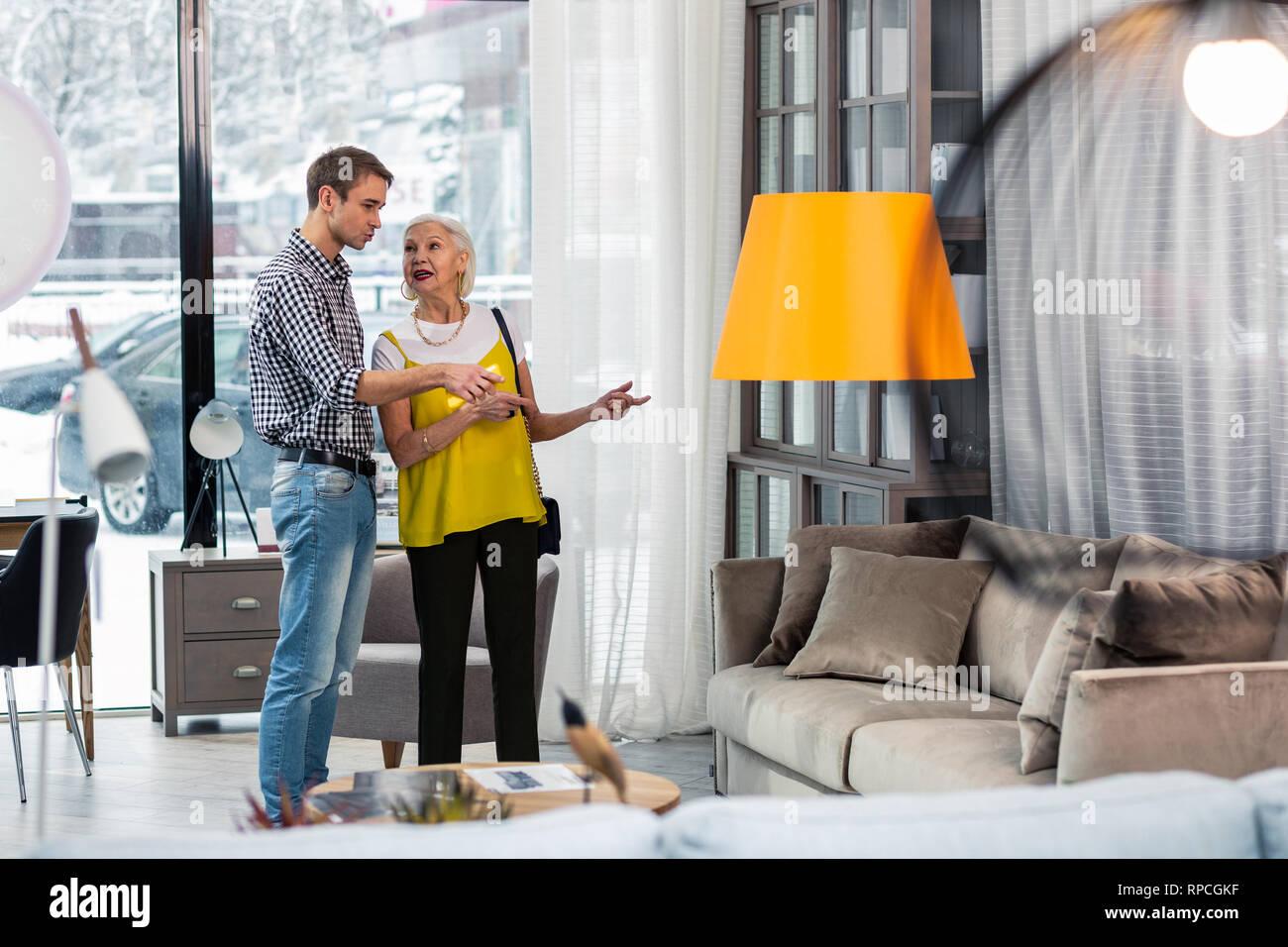 Bello figlio adulto discutendo divano acquisto con elegante anziani mom Foto Stock