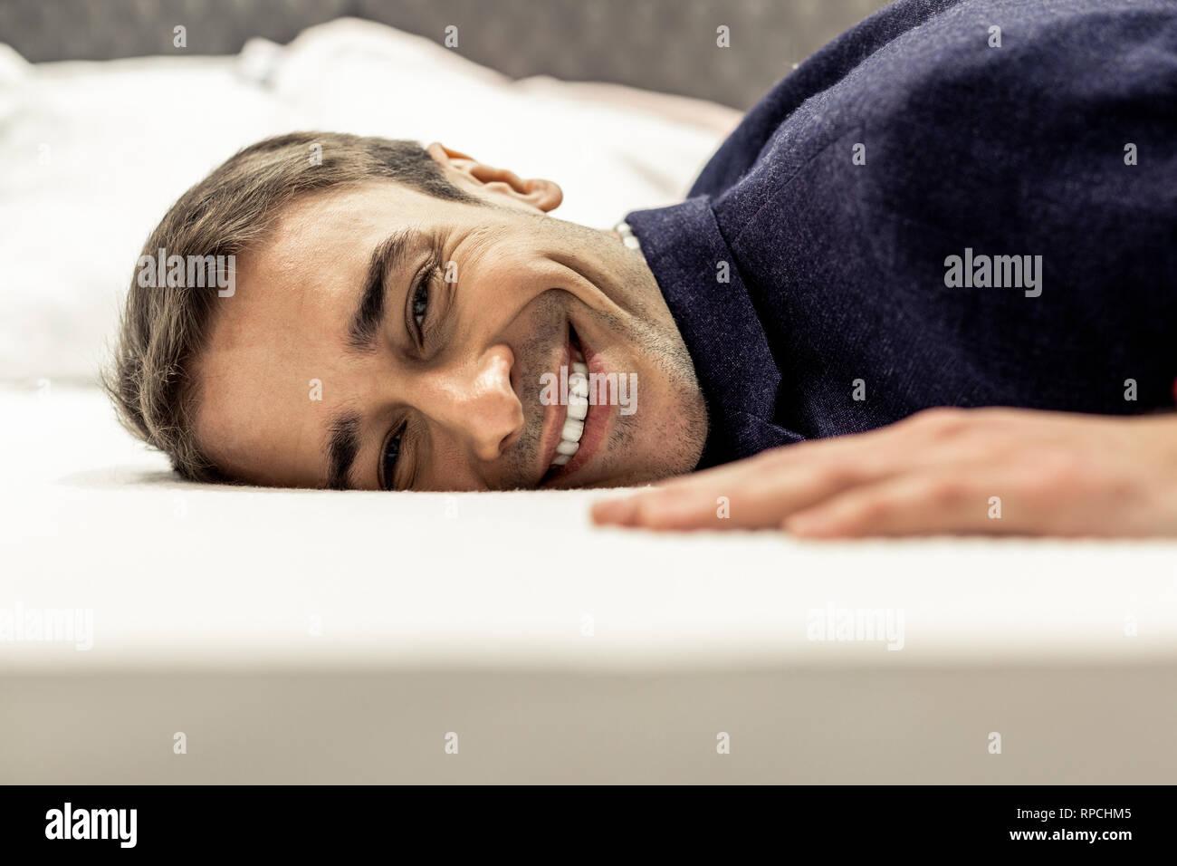 Ritratto di sorridente viso maschile giacente sul letto bianco fogli Immagini Stock