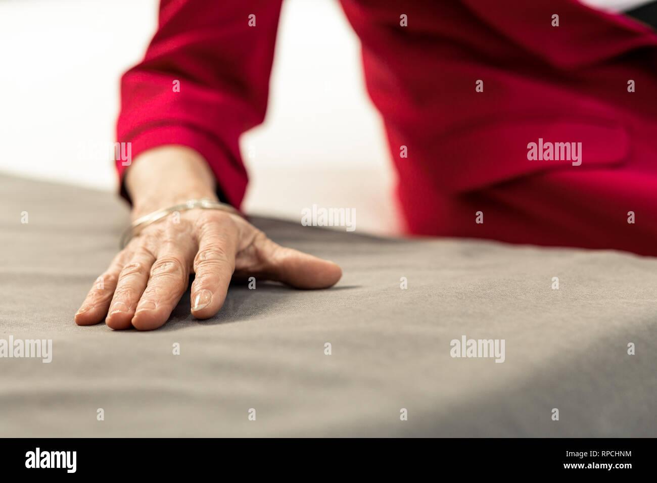 Ritratto di close-up di invecchiamento lady mano giacente sul letto di fogli Immagini Stock