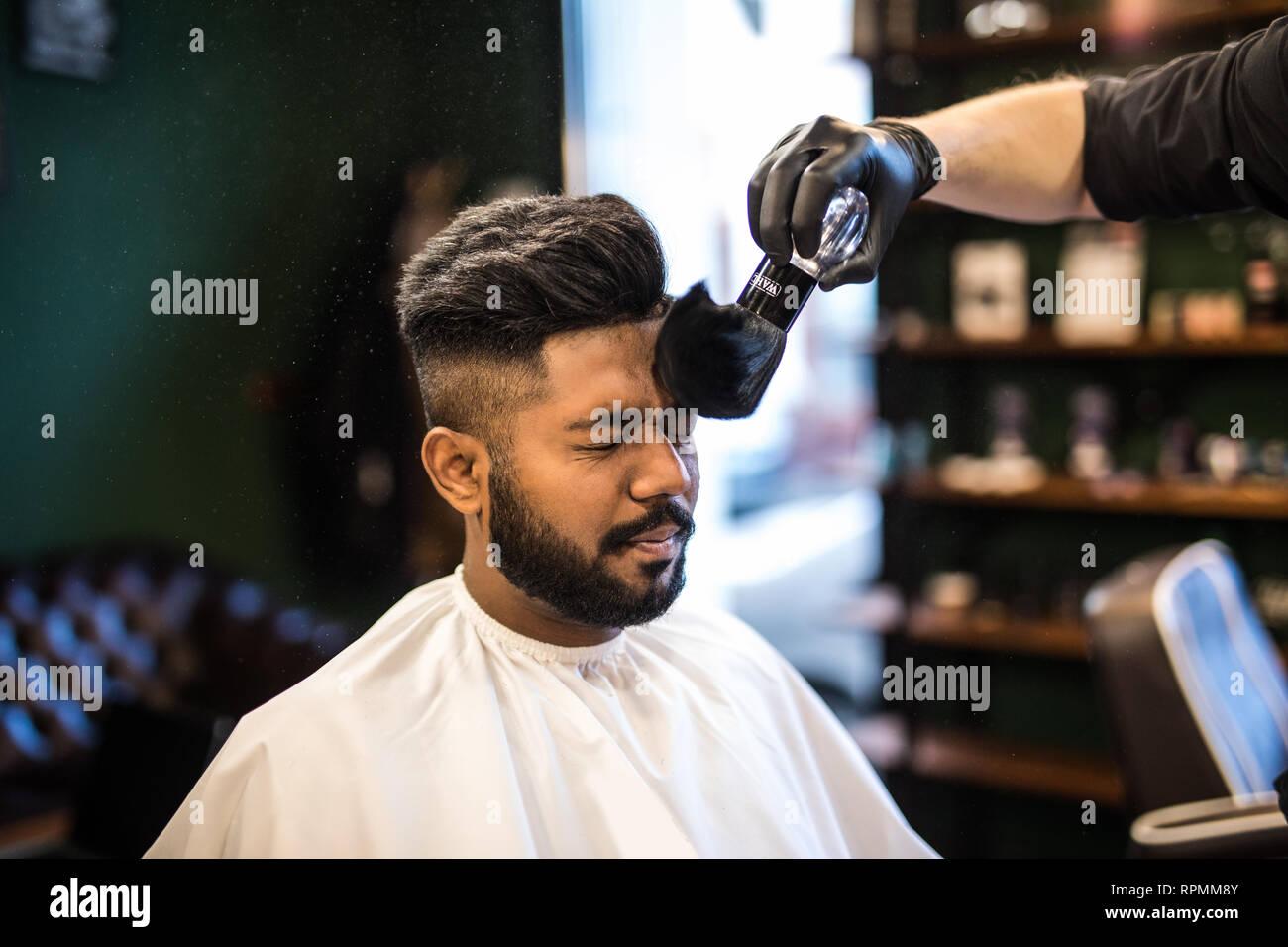 Barbieri mano diffusione di polvere di talco sui client il collo con professional Pennelli per barba in Barberia salon.maschio trattamento di bellezza concetto.giovane uomo nero ge Foto Stock