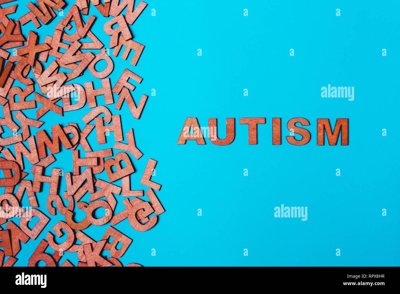 La parola autismo da lettere di legno su uno sfondo blu. Il problema è nella socializzazione, comunicazione Immagini Stock