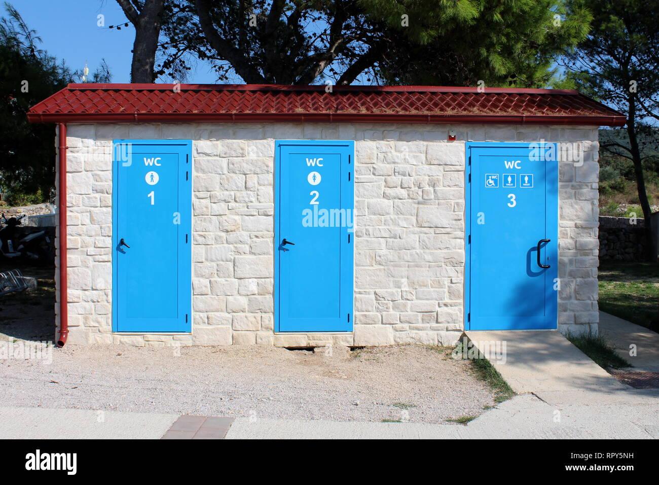 Outdoor spiaggia pubblica servizi igienici in una fila per uomo e donna di persone disabili in ben costruito nuove tradizionale struttura in pietra circondato con ghiaia Immagini Stock