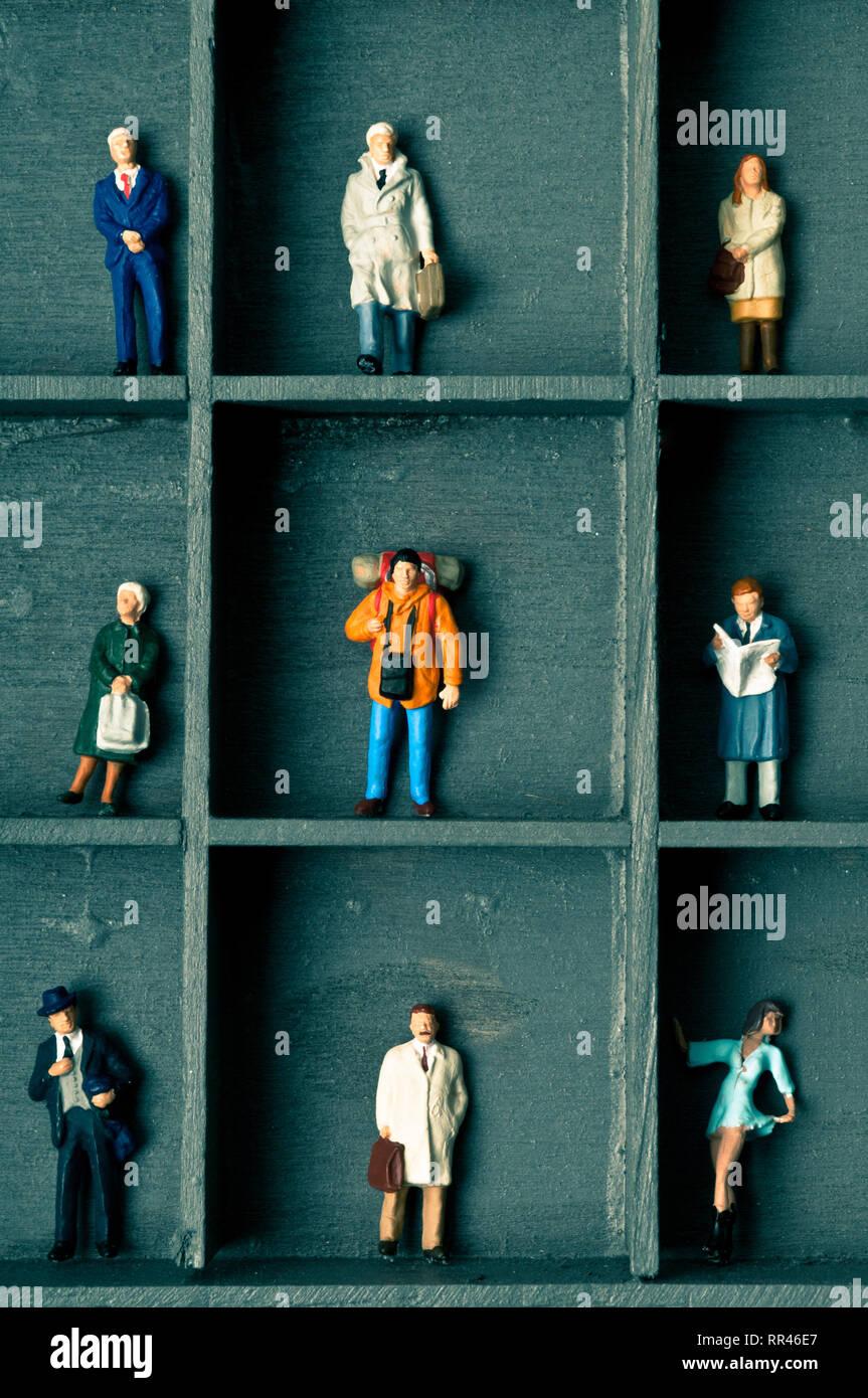 Statuine in miniatura in una scatola con vani, concetto per pigeonholing persone Immagini Stock