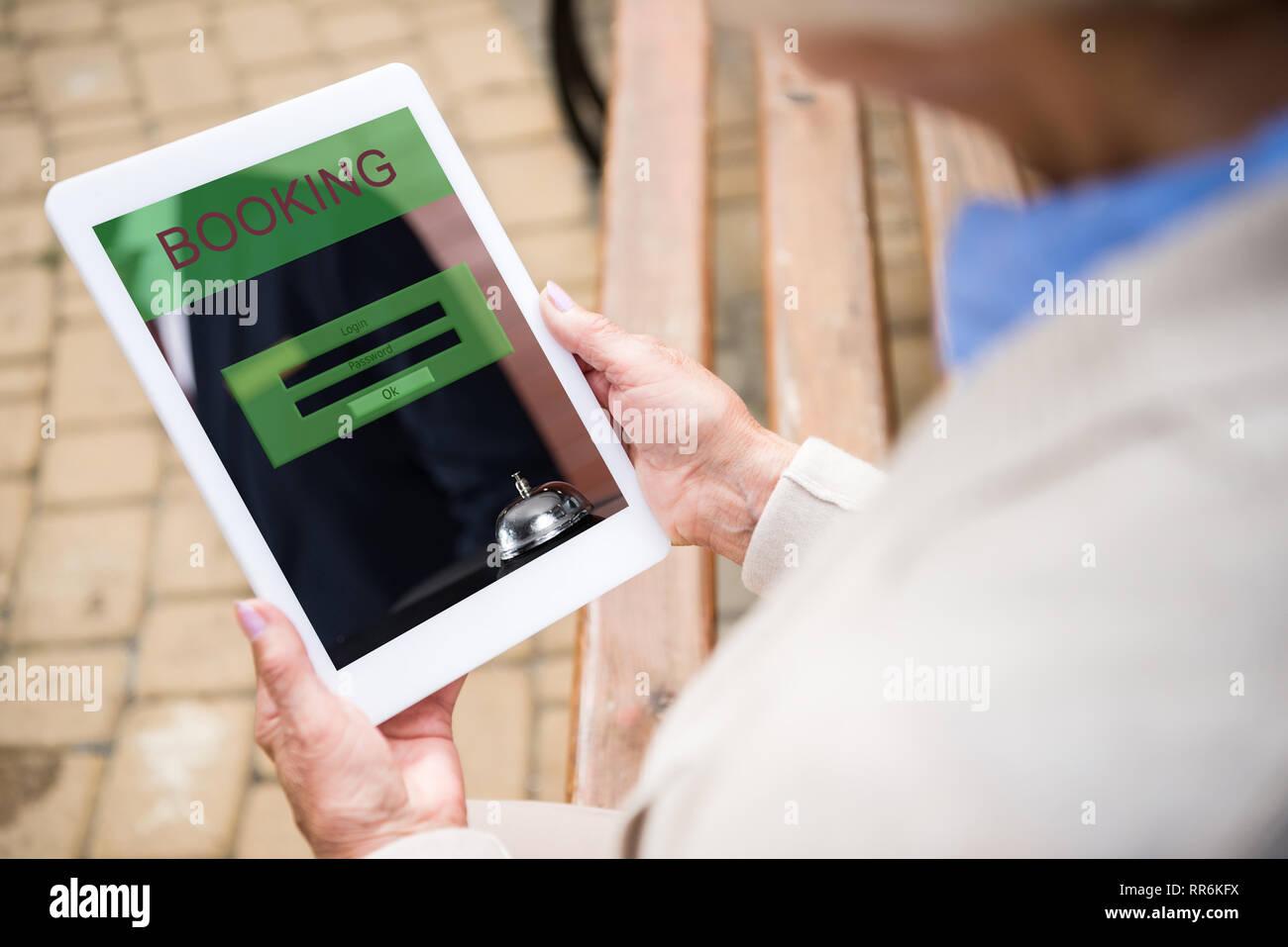 Messa a fuoco selettiva di senior donna utilizzando digitale tabella con prenotazione sullo schermo Immagini Stock