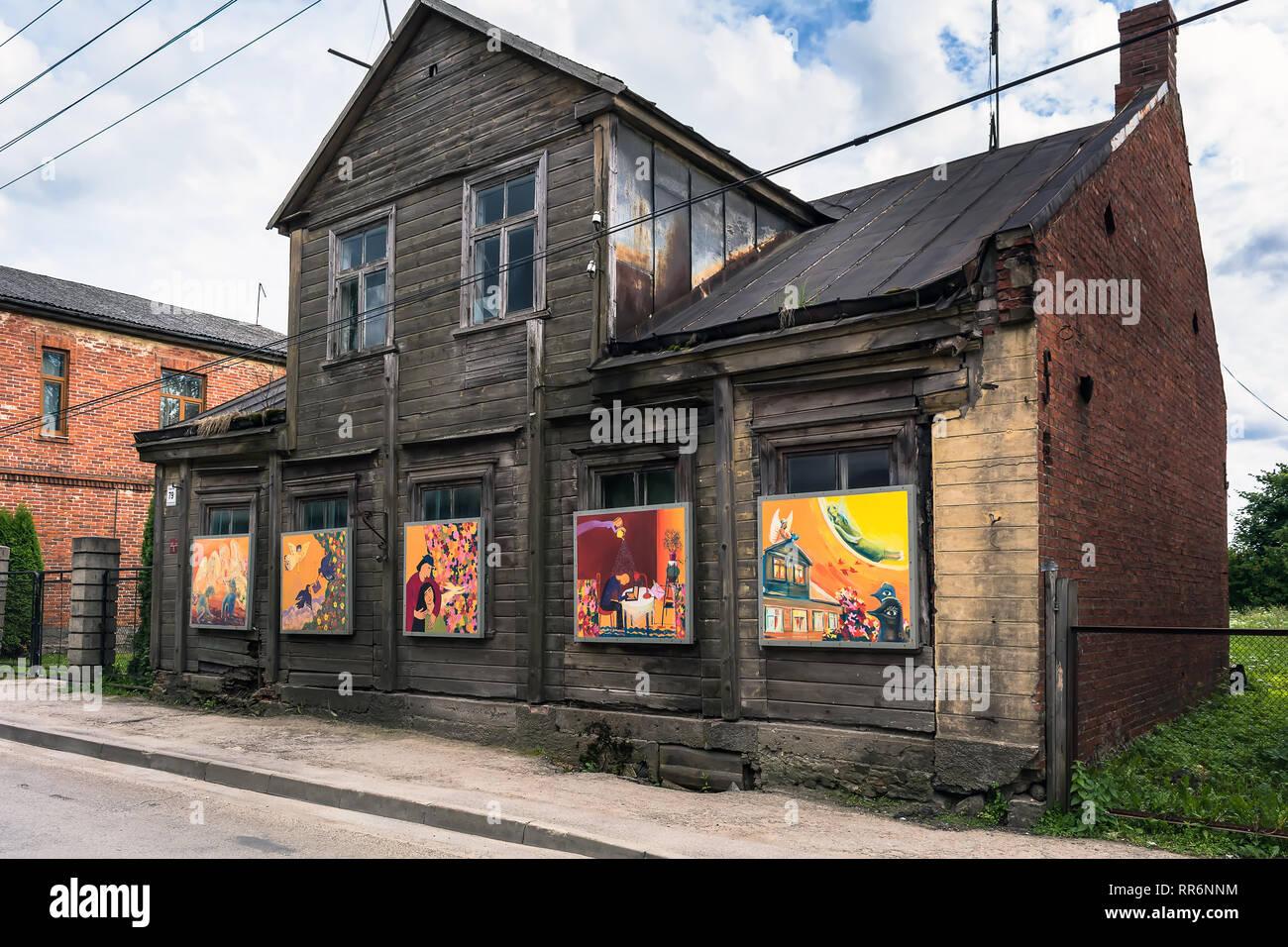 Jekabpils, Lettonia - 25 Giugno 2017: il vecchio abbandonato a due piani cupo edificio in legno con luminosi colorati dipinti invece di windows. Opposti e co Immagini Stock