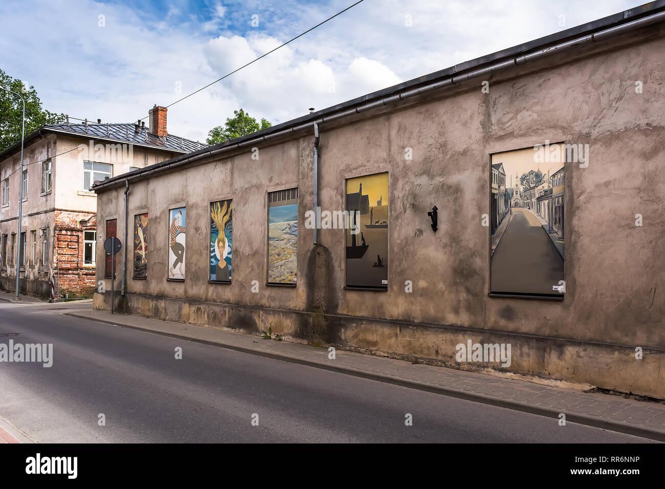 Jekabpils, Lettonia - 25 Giugno 2017: il vecchio abbandonato single-storey cupo edificio in pietra con luminosi colorati dipinti invece di windows. Opposti e Immagini Stock