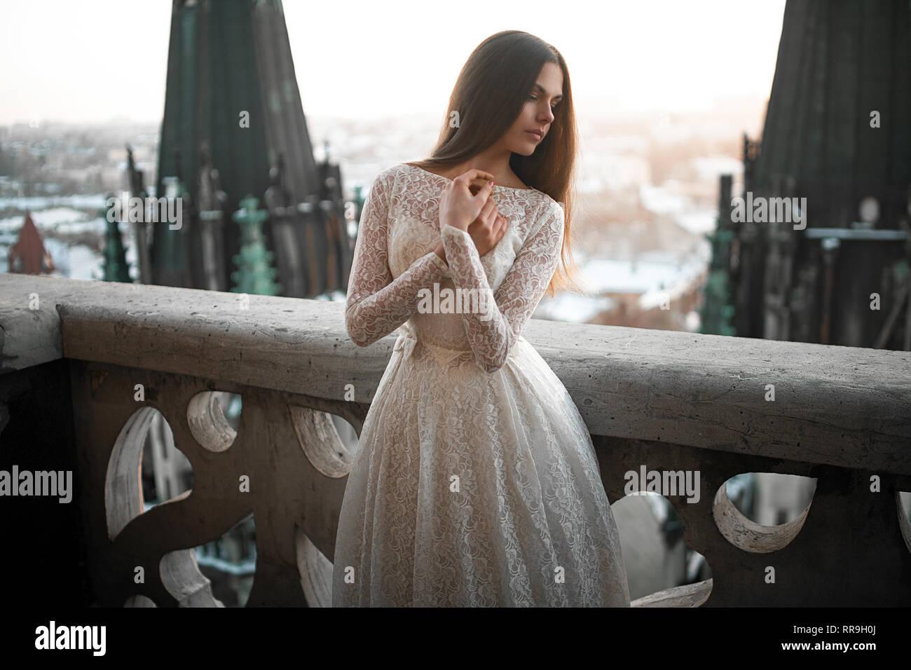 136c21f205a3 Bella giovane donna si erge in bianco lacy abiti sul balcone contro lo  sfondo del paesaggio
