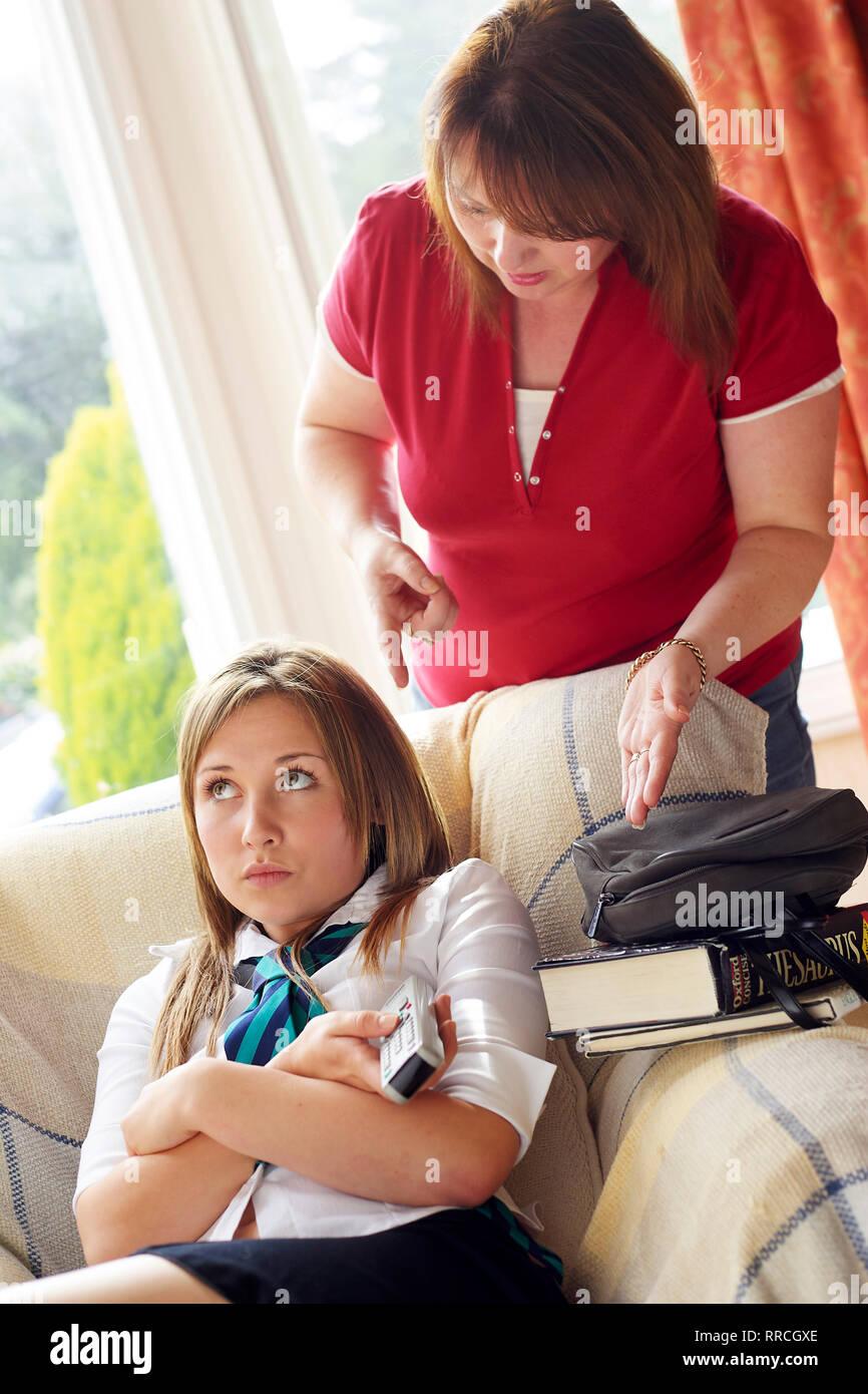 La madre racconta la sua figlia adolescente per eseguire i suoi compiti Immagini Stock