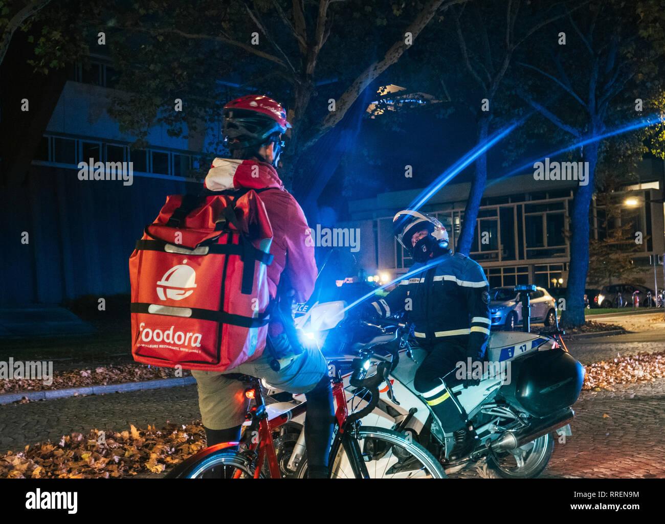 Strasburgo, Francia - Ott 27, 2018: Maschio funzionario di polizia bloccando la strada - Foodora ciclista a consegnare il cibo in attesa dovuta alla delegazione ufficiale visita Immagini Stock
