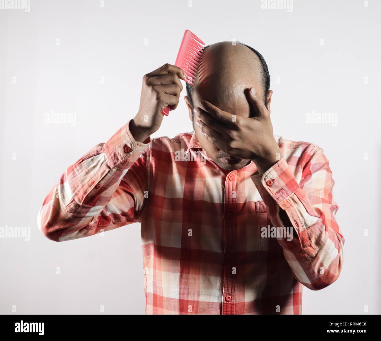 Uomo calvo che copre il suo volto nella vergogna a fondo bianco con spazio per il testo Immagini Stock