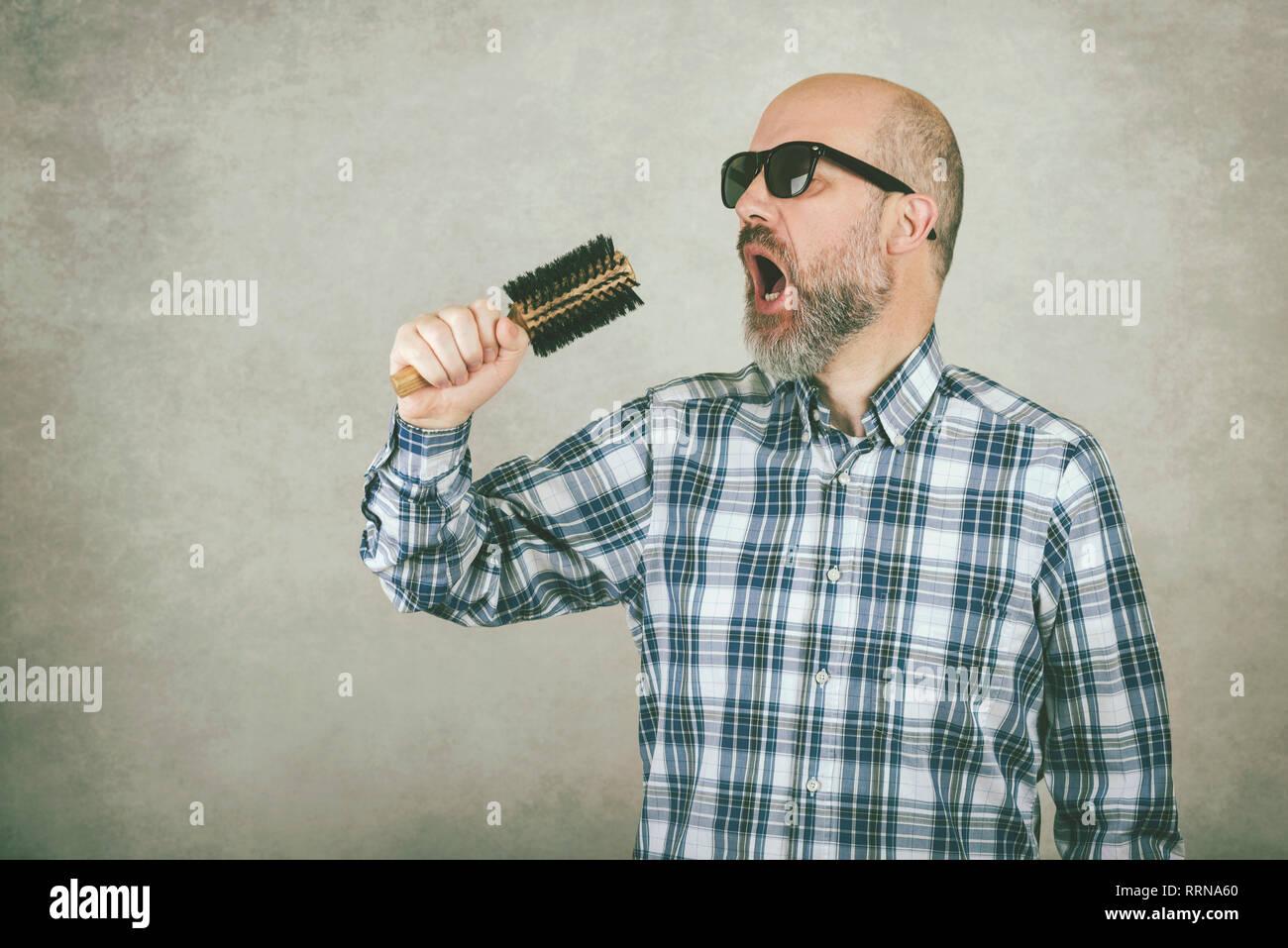 Uomo con occhiali da sole cantando una spazzola per capelli contro uno sfondo grigio Immagini Stock
