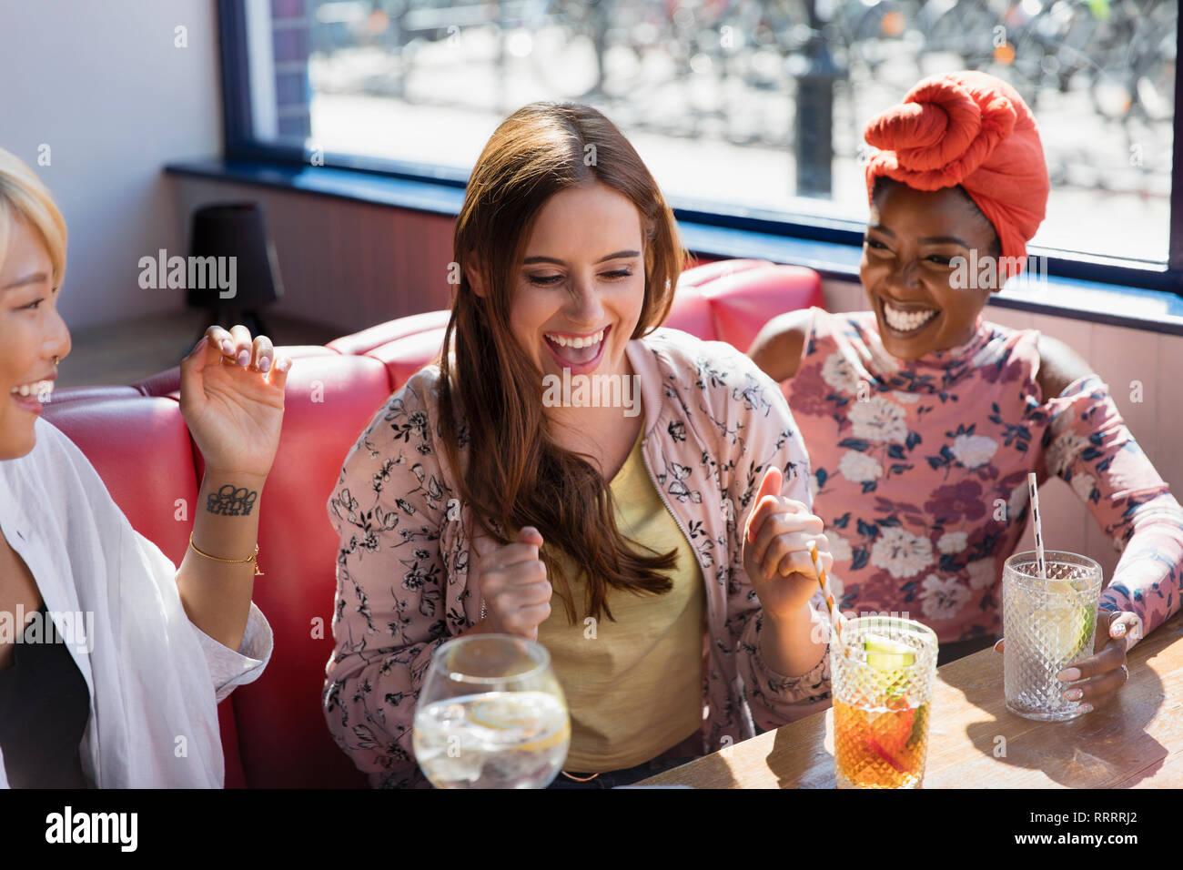 Felice, entusiasta delle giovani donne a bere un cocktail nel ristorante Foto Stock