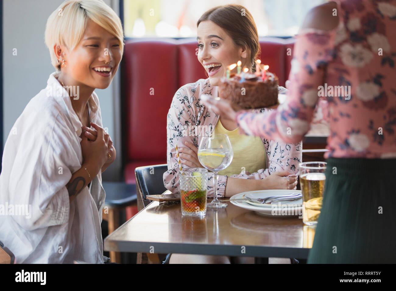 Entusiasti di donne giovani amici festeggia il compleanno con la torta nel ristorante Immagini Stock