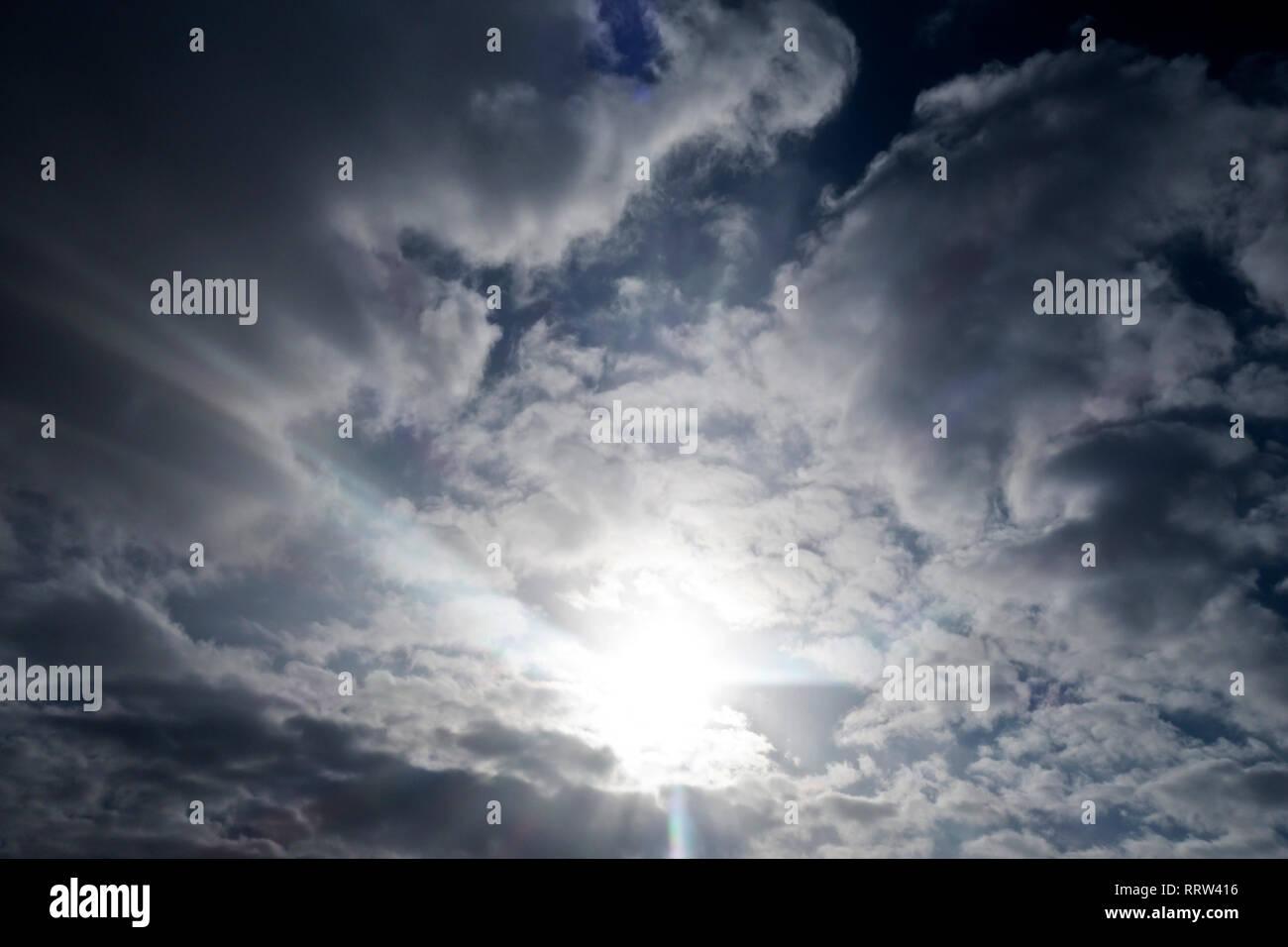 Cielo nuvoloso con sun spiata da dietro le nuvole, con raggi di luce quasi celeste Immagini Stock