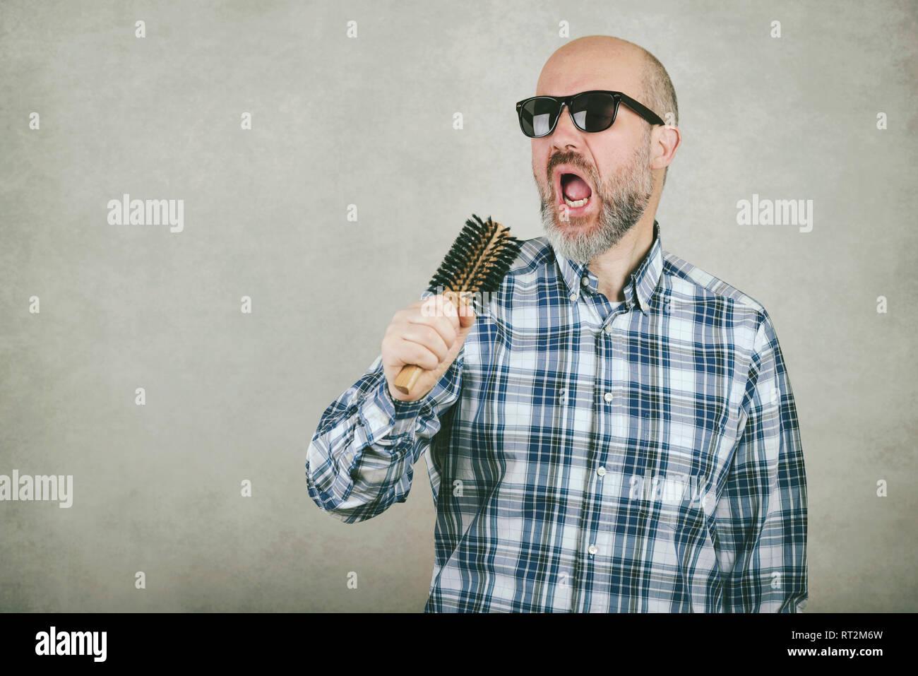 Uomo calvo con occhiali da sole cantando una spazzola per capelli contro uno sfondo grigio Immagini Stock