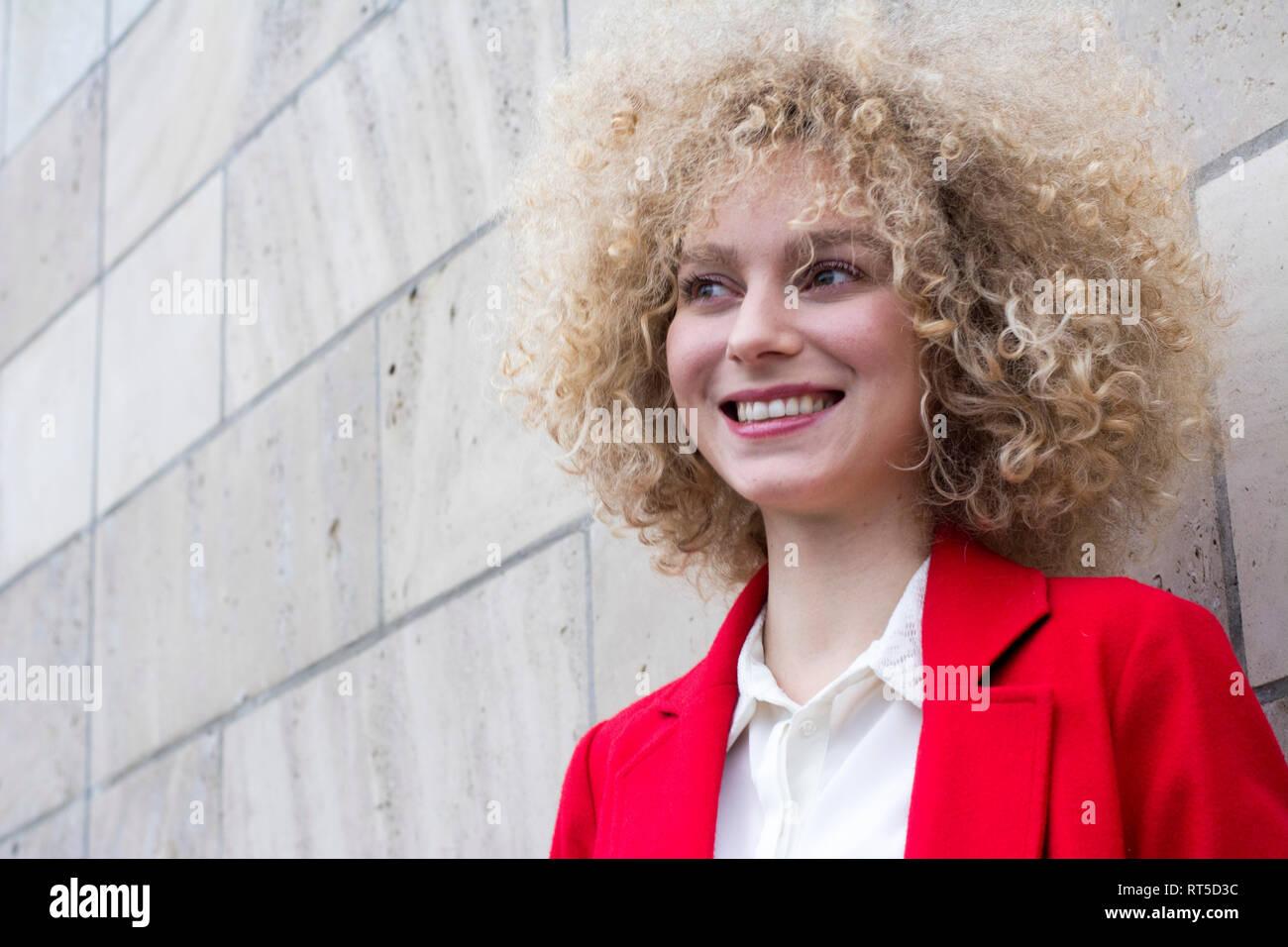 Ritratto di ridere donna bionda con boccoli Foto Stock