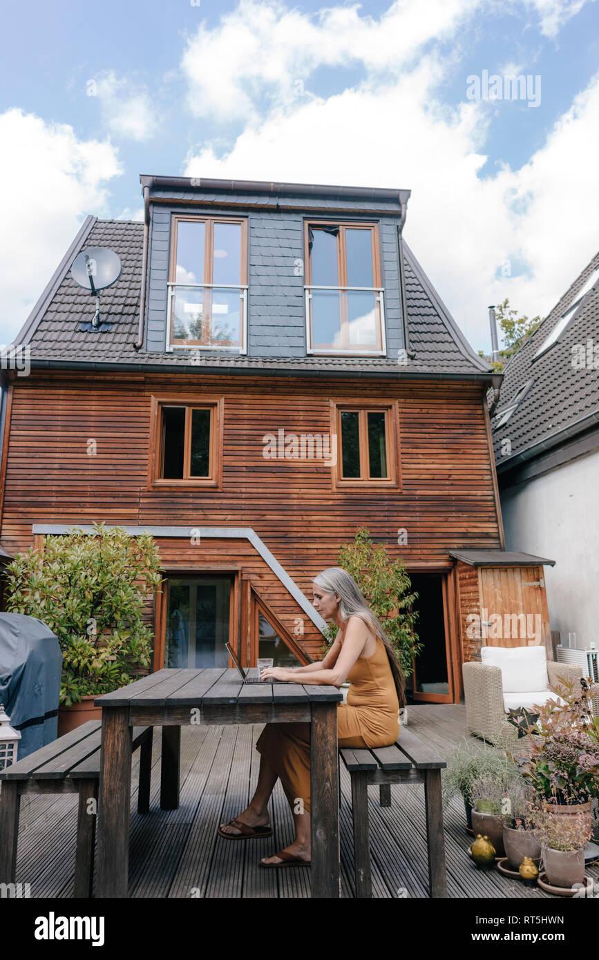 Donna seduta sulla terrazza di casa sua utilizzando laptop Foto Stock