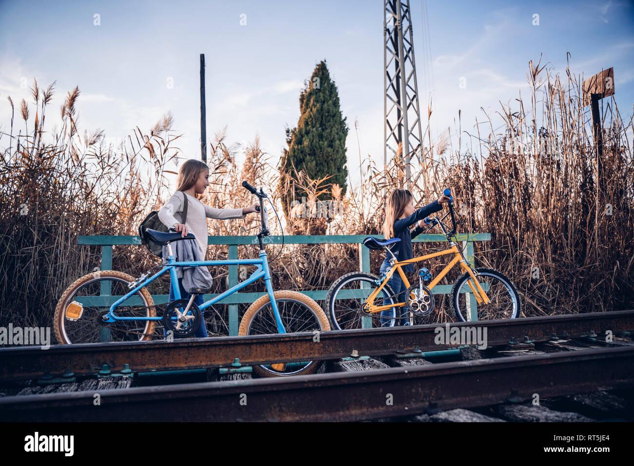 Due ragazze di camminare sulla via treno con le biciclette Foto Stock