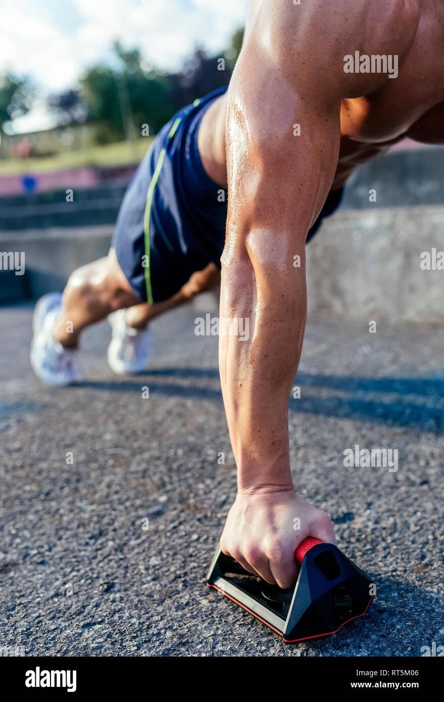 Close-up di barechested uomo muscolare facendo push-up all'aperto Foto Stock