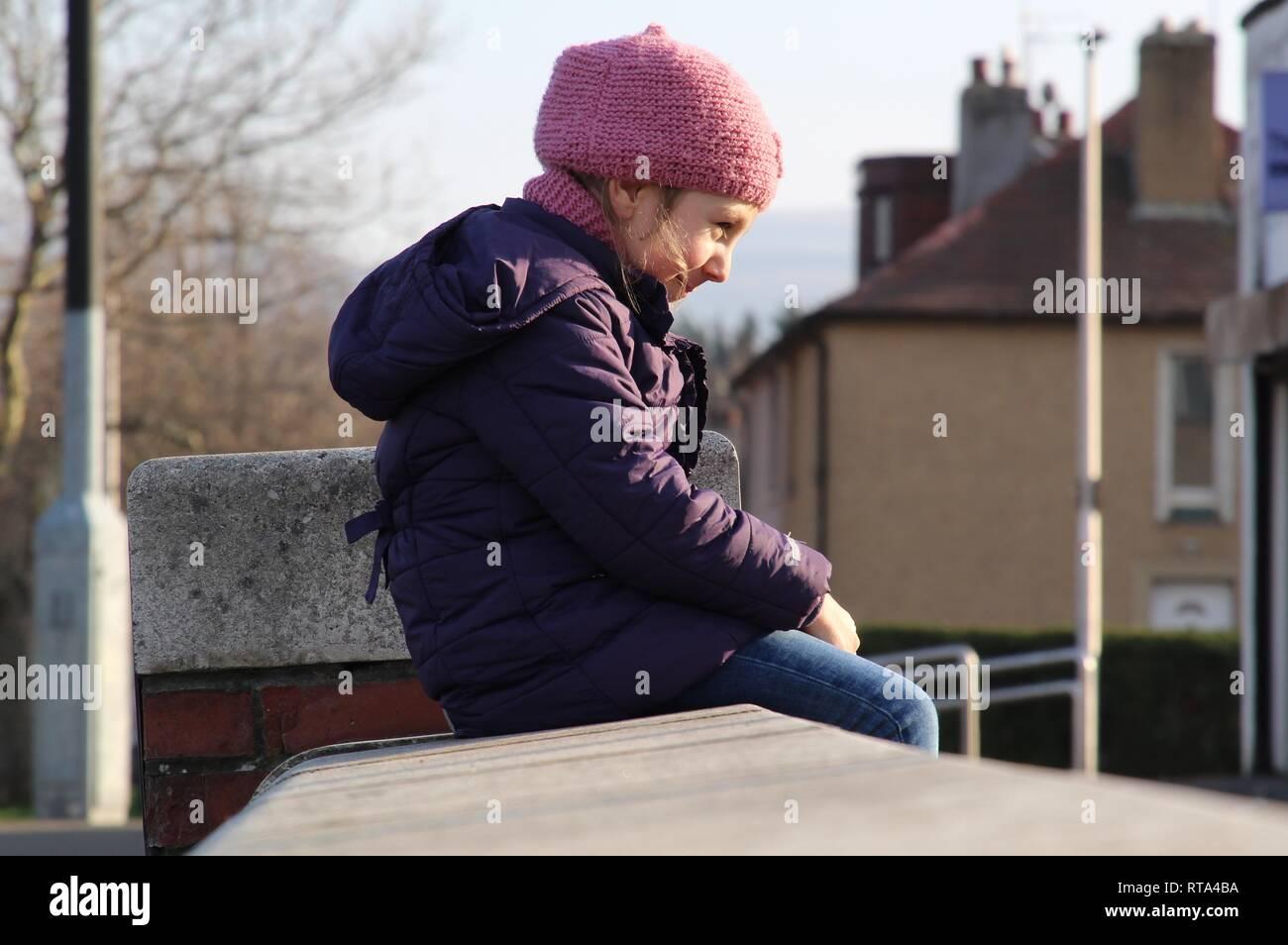 Sorridenti bambino seduto al sole Immagini Stock
