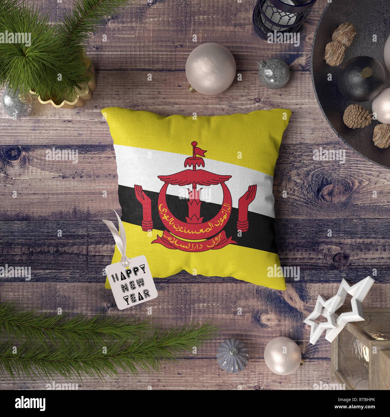 Felice Anno Nuovo tag con il Brunei bandiera sul cuscino. Decorazione di Natale concetto sul tavolo di legno con incantevoli oggetti. Immagini Stock