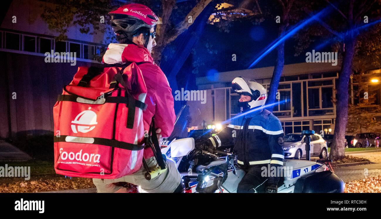 Strasburgo, Francia - Ott 27, 2018: Polizia gendarmerie bloccando la strada - Foodora ciclista a consegnare il cibo in attesa dovuta alla delegazione ufficiale visita Immagini Stock