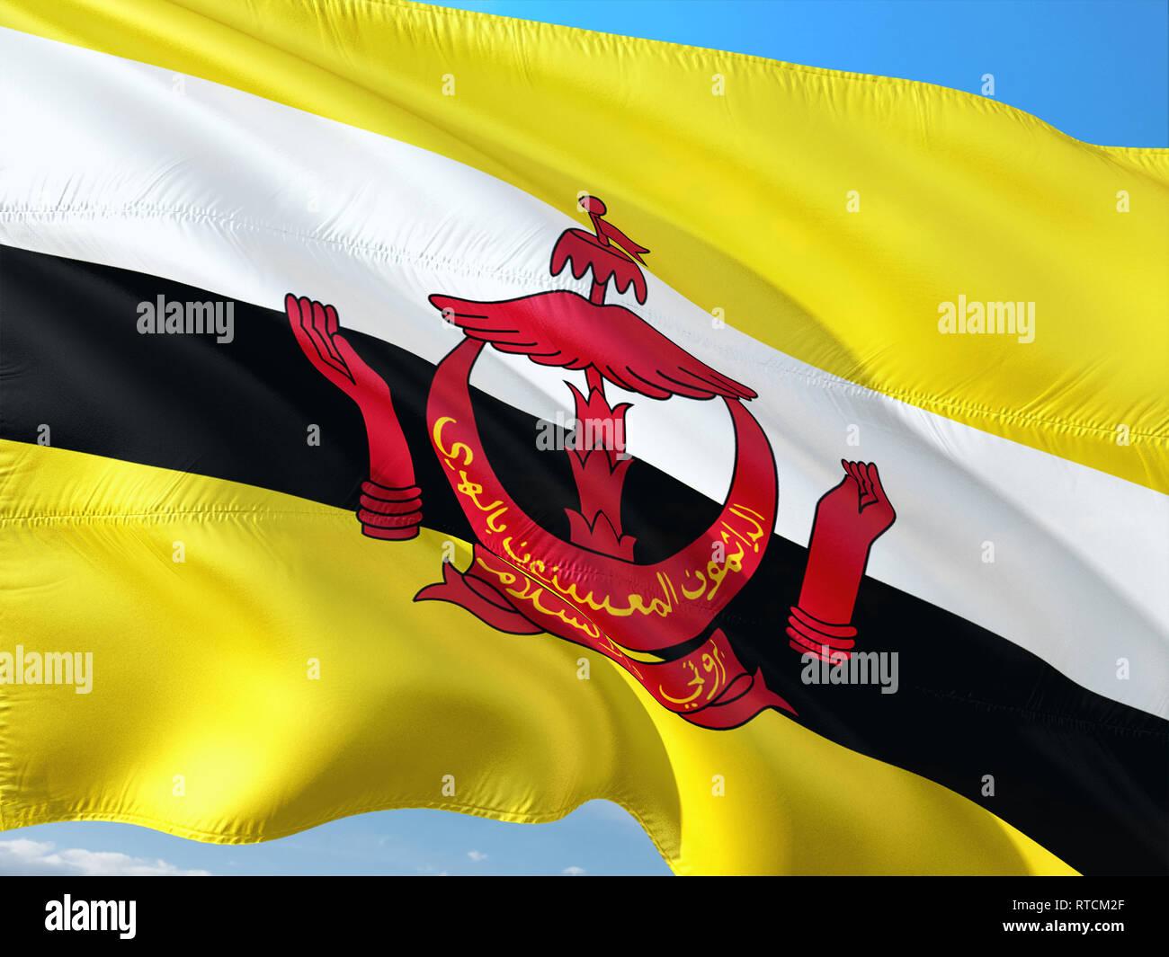 Bandiera del Brunei sventolare nel vento contro il profondo blu del cielo. Alta qualità tessuto. Immagini Stock