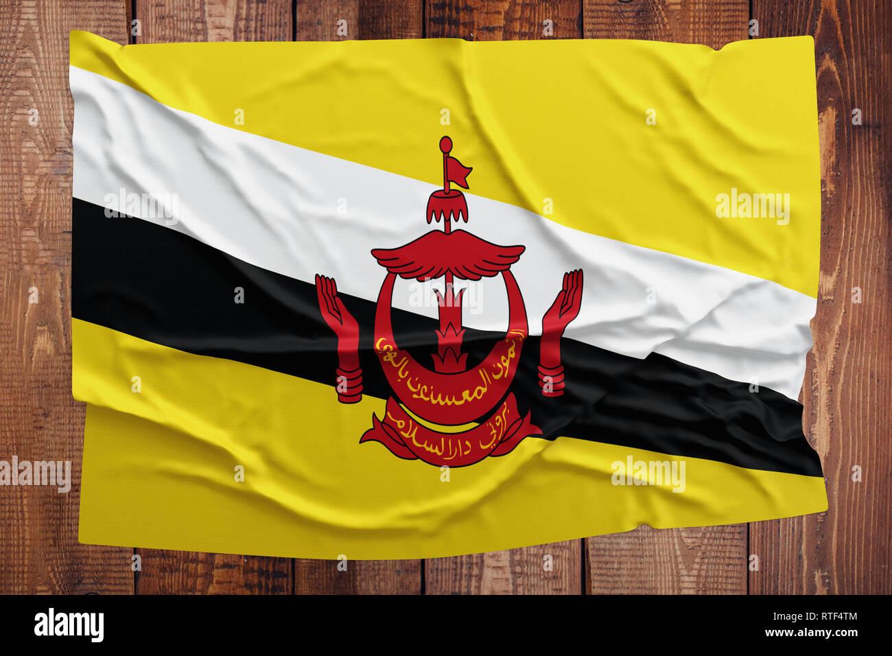 Bandiera del Brunei su una tavola di legno dello sfondo. Bruneian stropicciata bandiera vista dall'alto. Immagini Stock