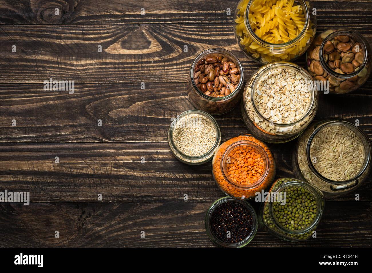 Cereali, legumi e fagioli in vasetti di vetro scuro su un tavolo di legno. Foto Stock
