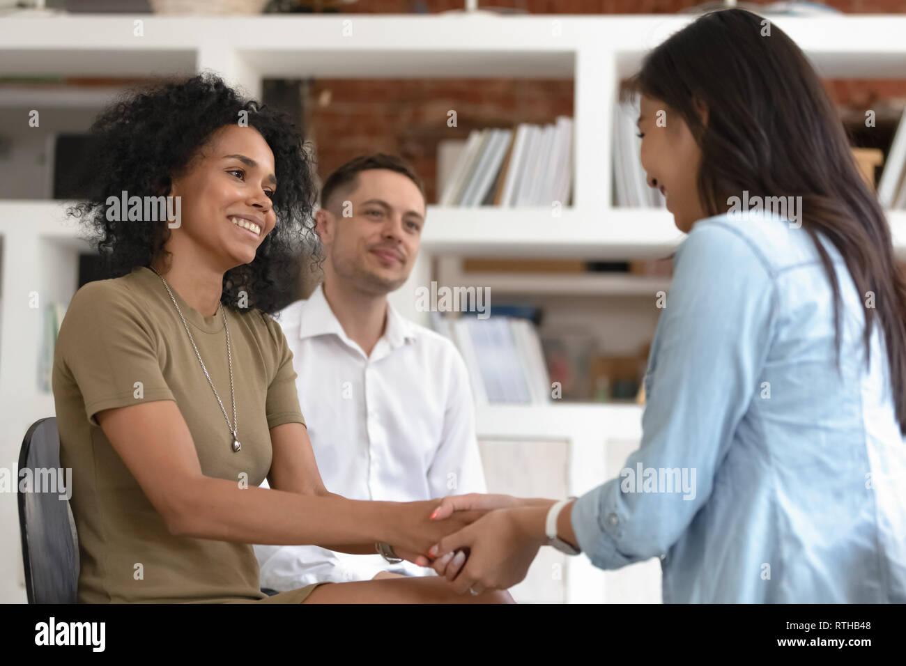 Asiatici e africani le donne tenendo le mani durante la terapia di gruppo a sessione Immagini Stock