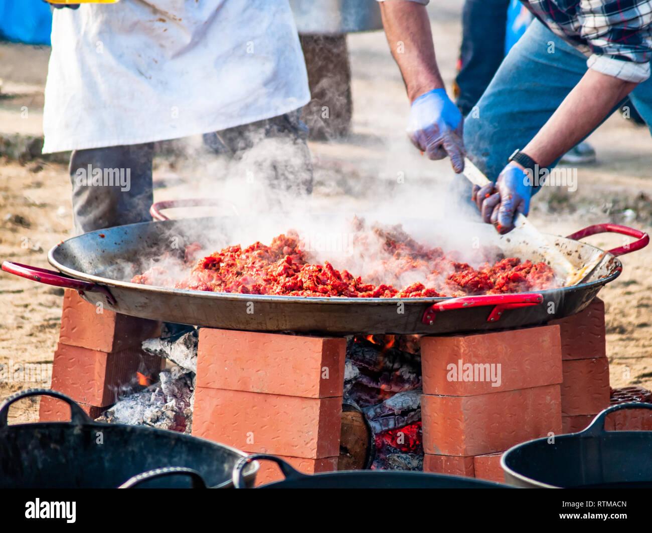 Persona non riconoscibile per la cottura del cibo tradizionale chiamato chichas sulla strada di un partito popolare in un villaggio in Spagna Immagini Stock