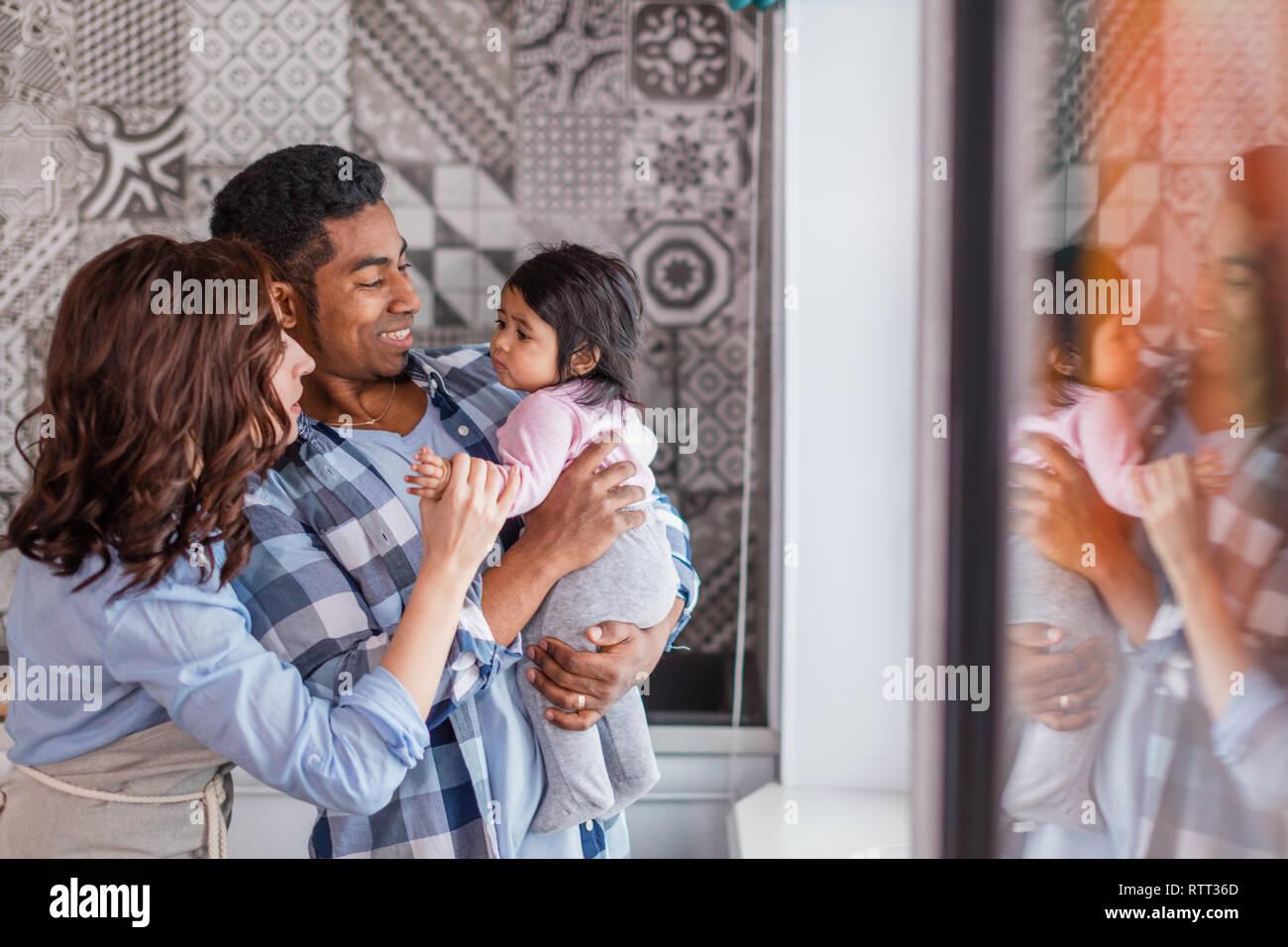 Giovane coppia positiva a giocare con il loro bambino a casa, amore, famiglia amichevole concetto, spazio di copia Foto Stock