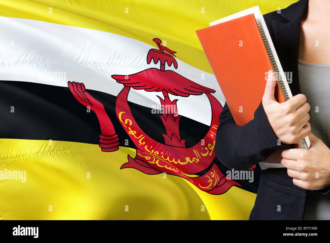 Apprendimento della lingua Bruneian concetto. Giovane donna in piedi con la bandiera del Brunei in background. Docente in possesso di libri, arancione sbozzato per la copertina del libro. Immagini Stock