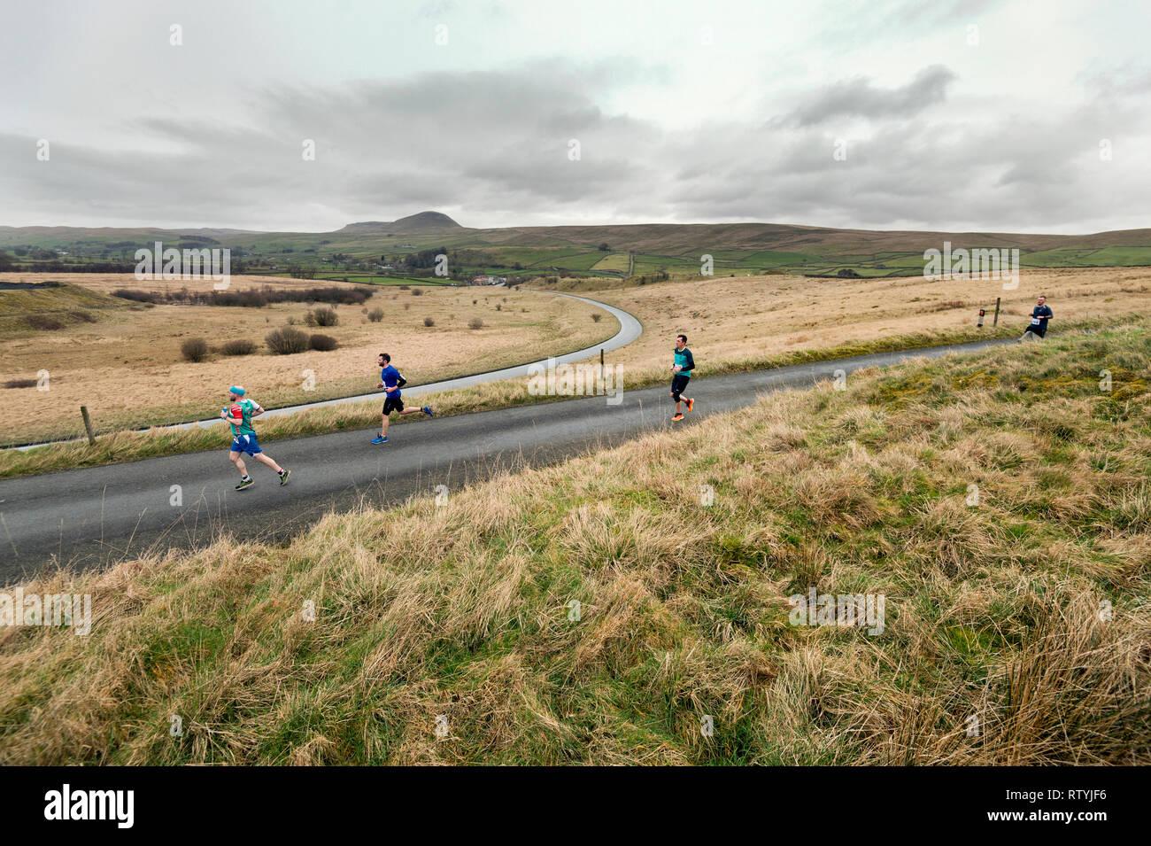 Settle, North Yorkshire, Regno Unito. 03 marzo, 2019. Settle mezza maratona. Pass guide ponte Helwith nel Yorkshire Dales National Park. Pen-y-Ghent picco è visto all'orizzonte. Credito: John Bentley/Alamy Live News Immagini Stock