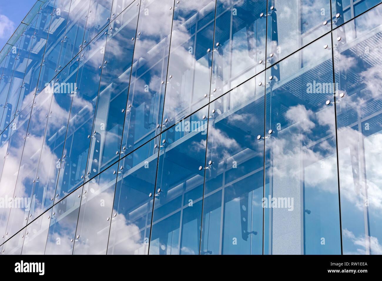 Nuvole riflettono sulla facciata in vetro e la parete di un ufficio moderno edificio. esterno del grattacielo in stile contemporaneo Foto Stock