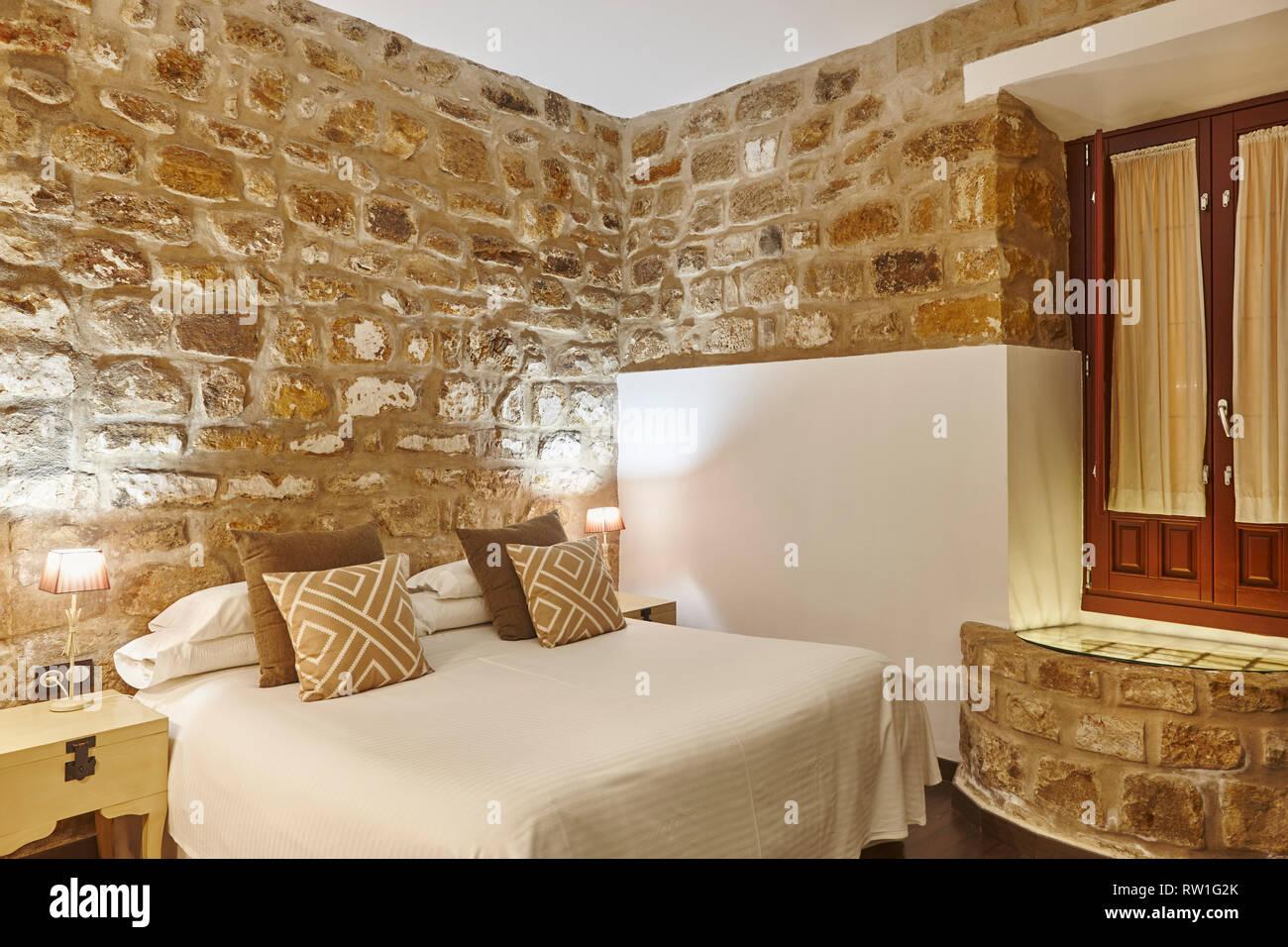Camera da letto con pareti di pietra. Hotel moderno e confortevole ...