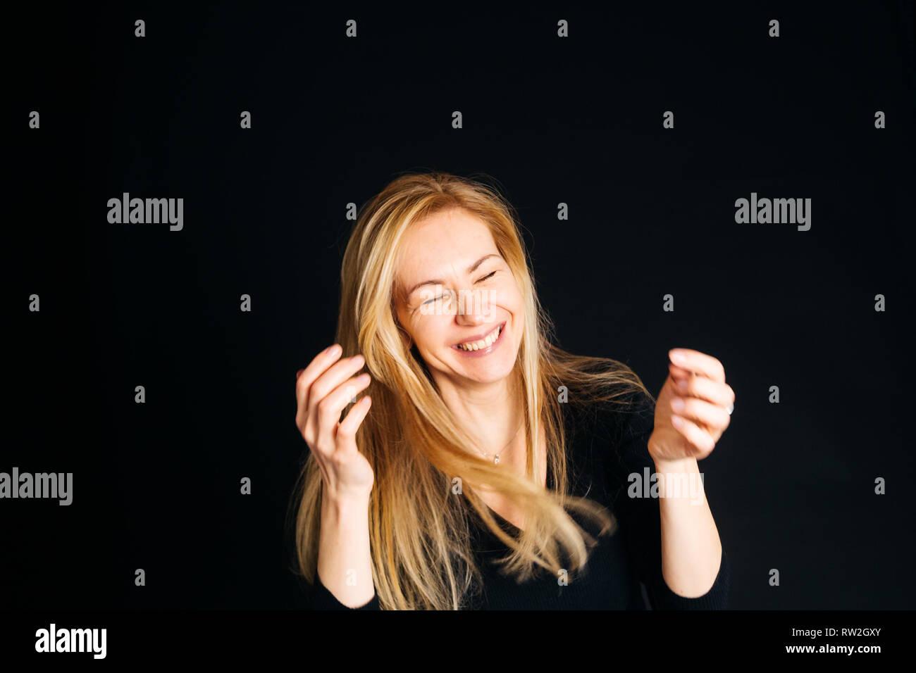 Close up studio ritratto di una bella donna in abito nero, ridendo a occhi chiusi sullo sfondo nero Foto Stock