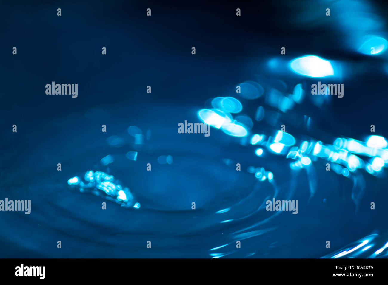 Splash di gocce di acqua su una superficie di acqua colorata con inchiostro celesti. Concetto di purezza, pulizia e conservazione delle risorse non rinnovabili. Abstr Immagini Stock