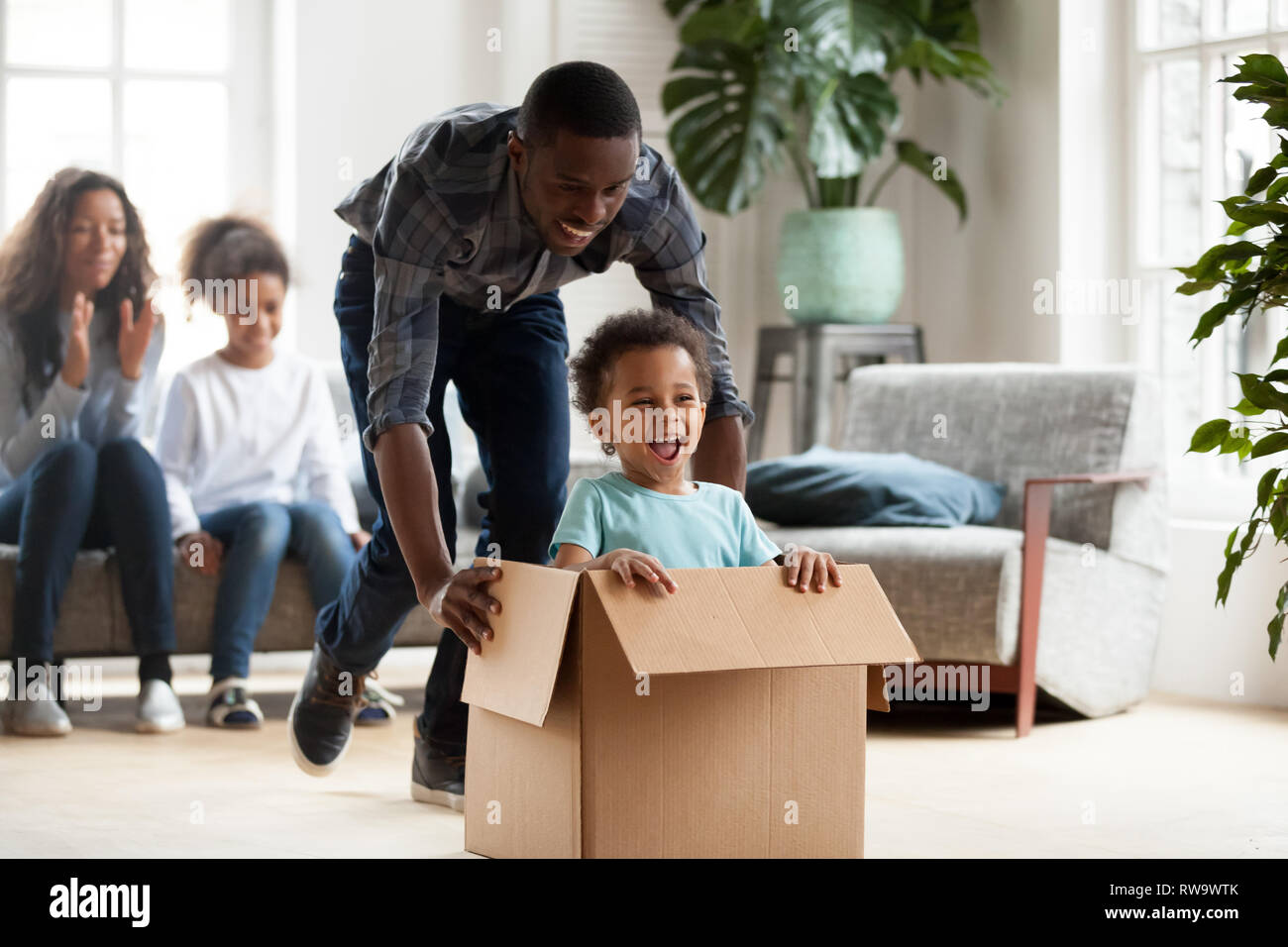 Felice famiglia nero gioca con i ragazzi in movimento per la casa nuova Immagini Stock