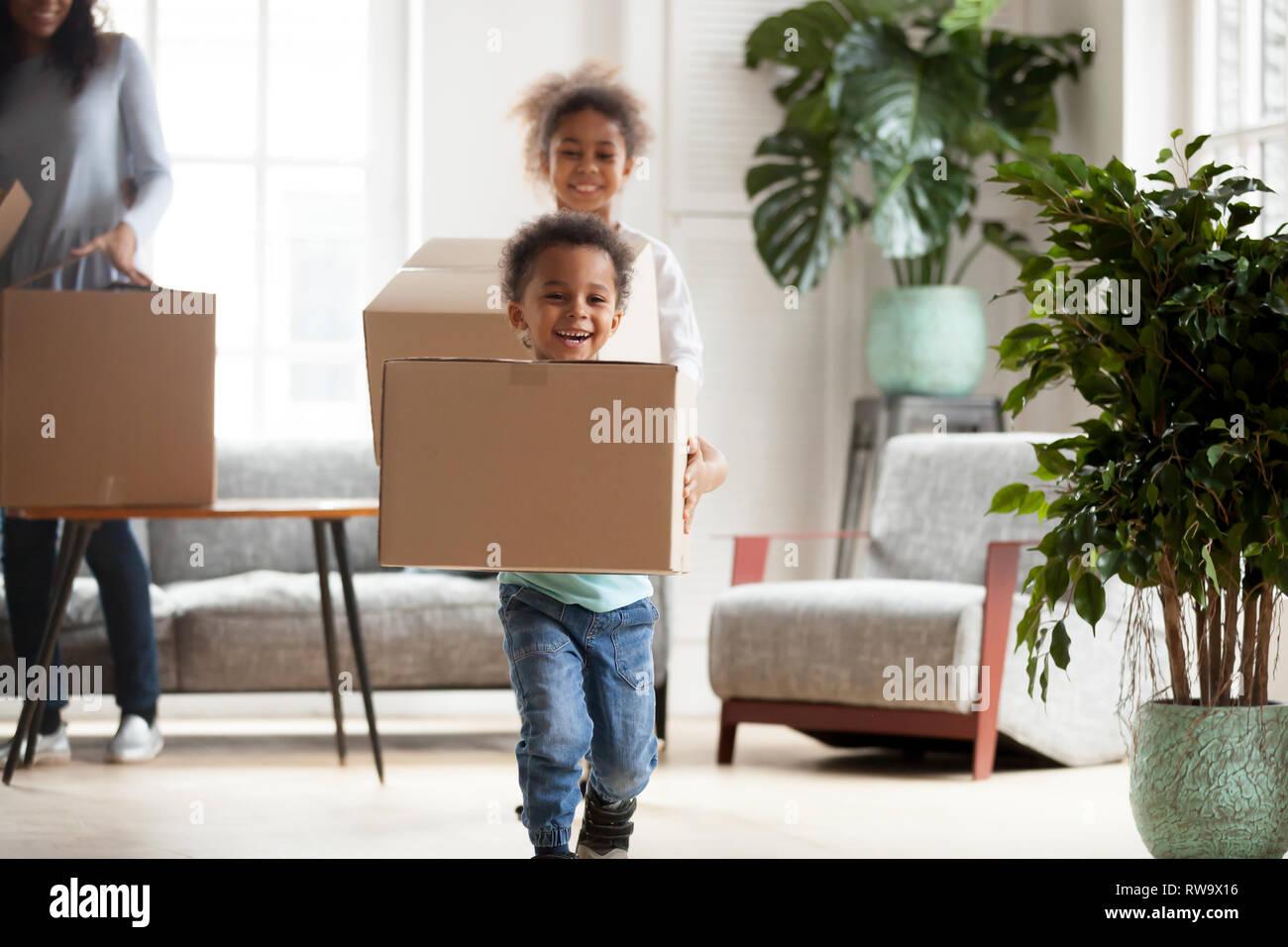 Emozionato piccolo nero kids con scatole happy per spostare in Immagini Stock