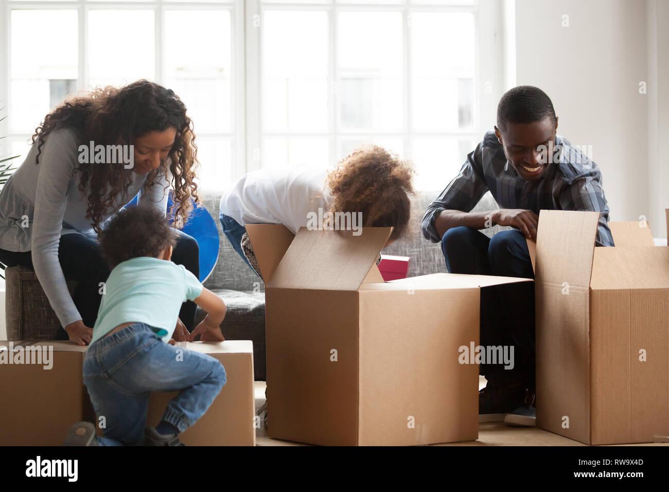 Nero felice famiglia con bambini piccoli disimballare le caselle Immagini Stock