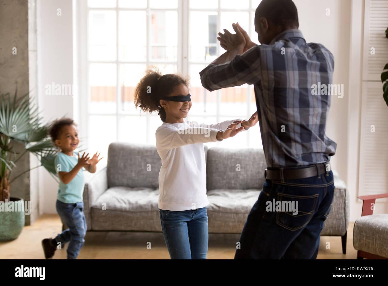 Piccola ragazza bendati giocare a nascondino con la famiglia Immagini Stock