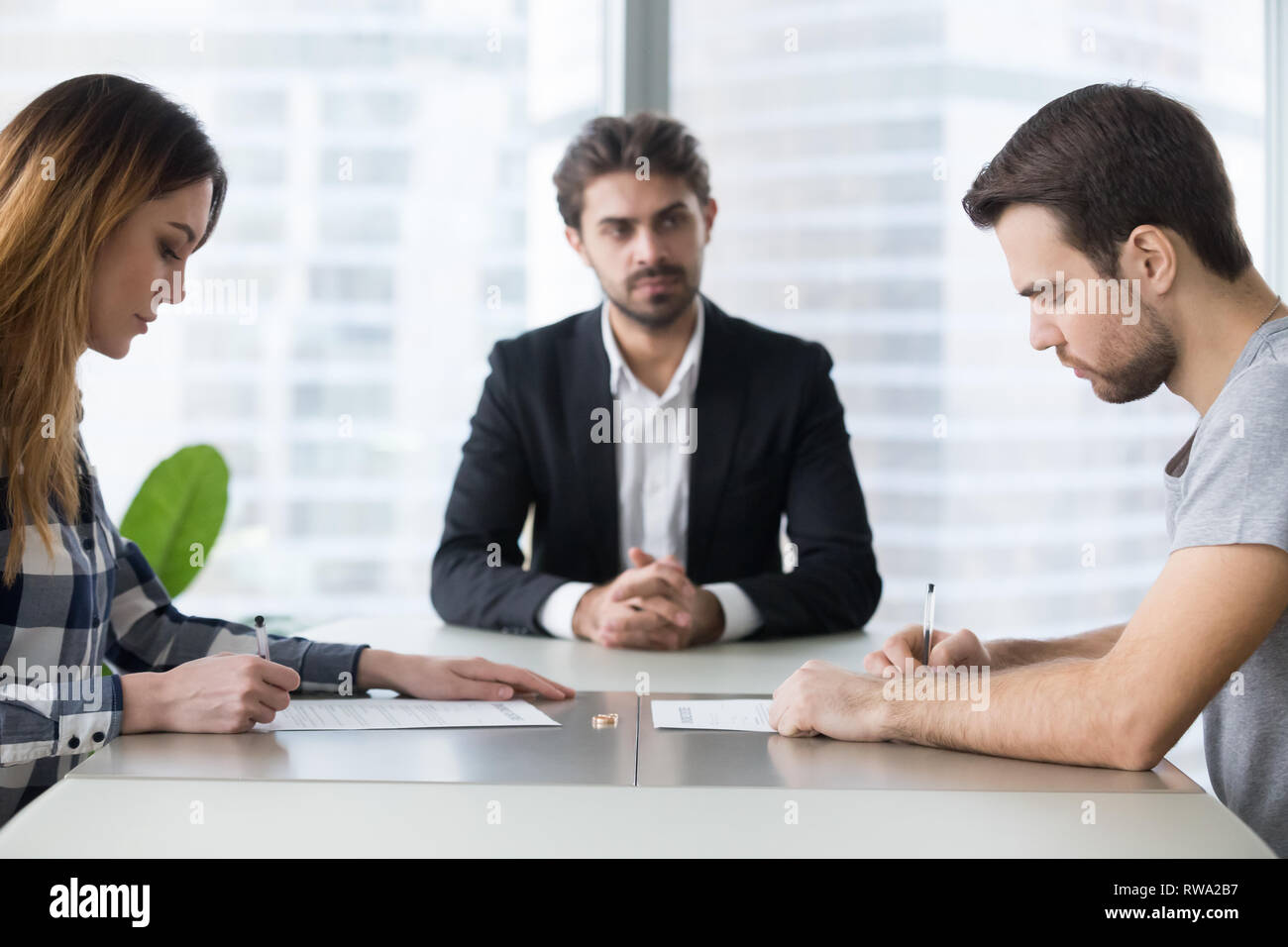 I coniugi giovane firma decreto paper Getting divorziati in avvocati office Immagini Stock