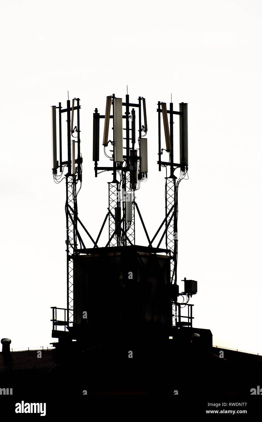 Sito di cella sul tetto di un edificio in silhouette Immagini Stock