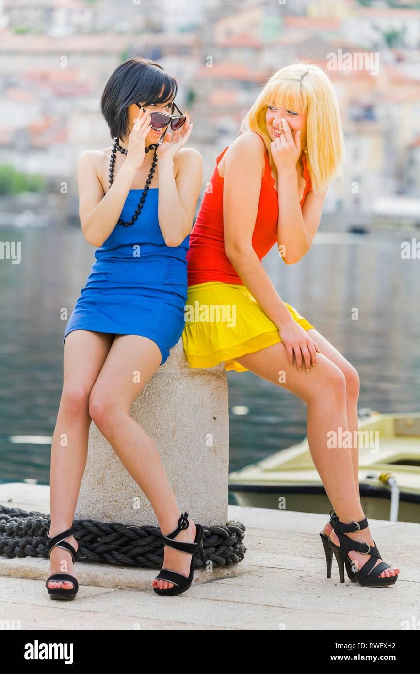 7cd06ec8dbfd Le ragazze adolescenti due amiche sul mare vestito in abiti corti mini  gonne peeking lookingabove occhiali